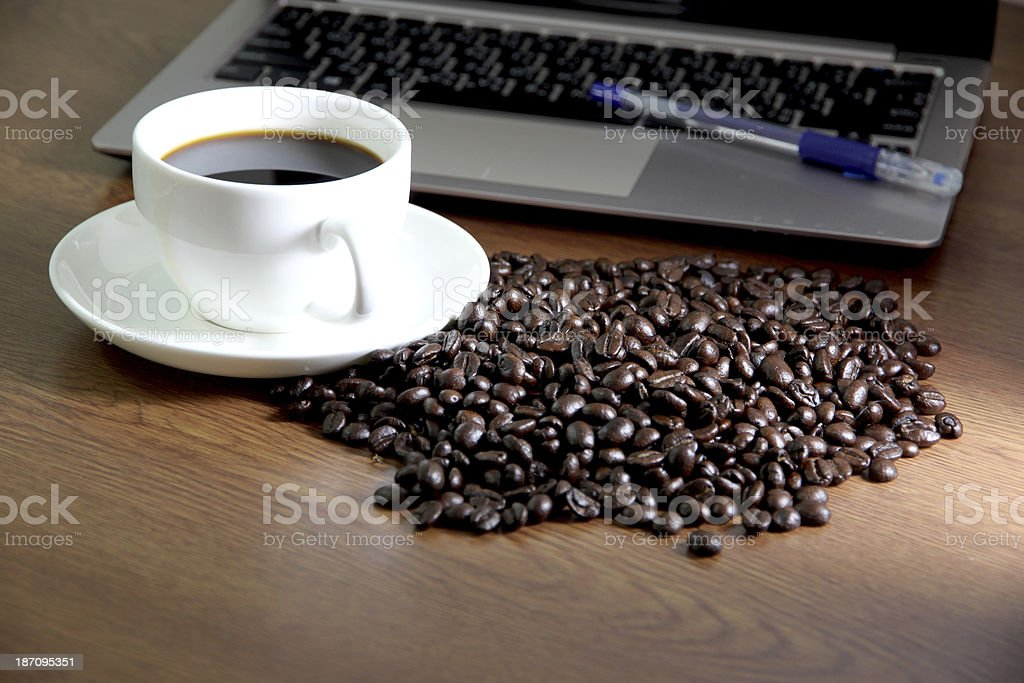 Coffee in white cup nearby the computer notebook. royalty-free stock photo