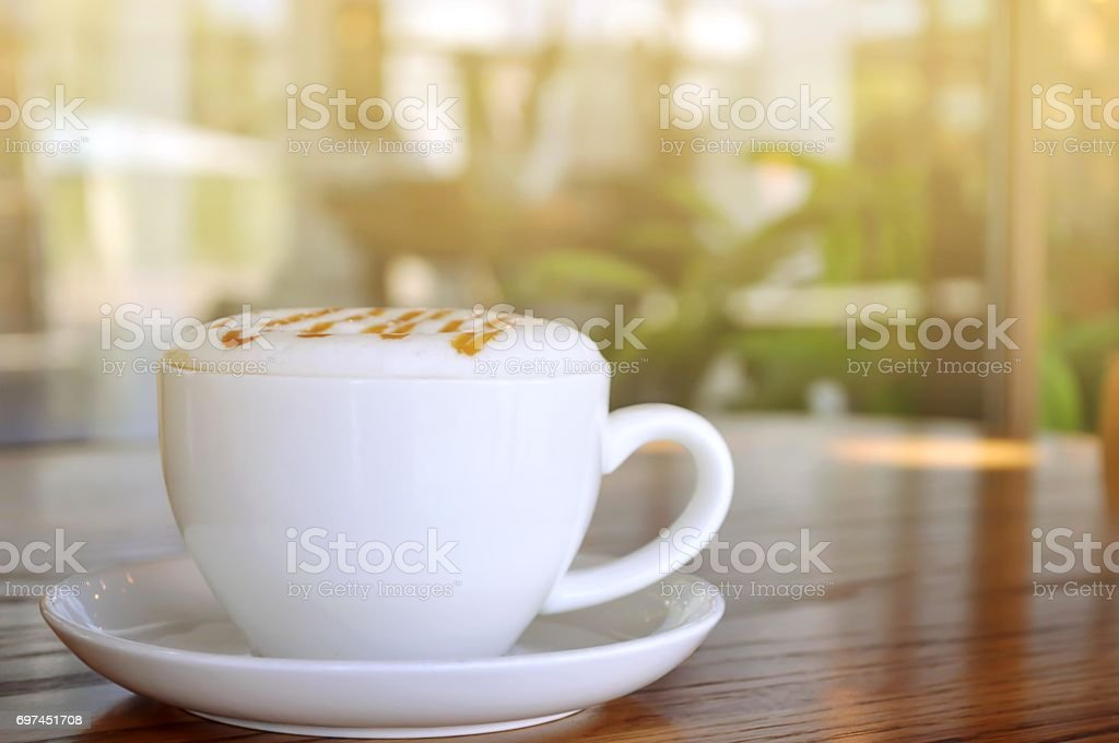 Coffee in white cup with sunlight on table wooden. stock photo