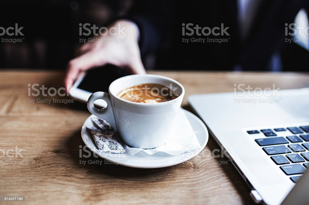 Coffee, laptop and phone, all set for work. stock photo