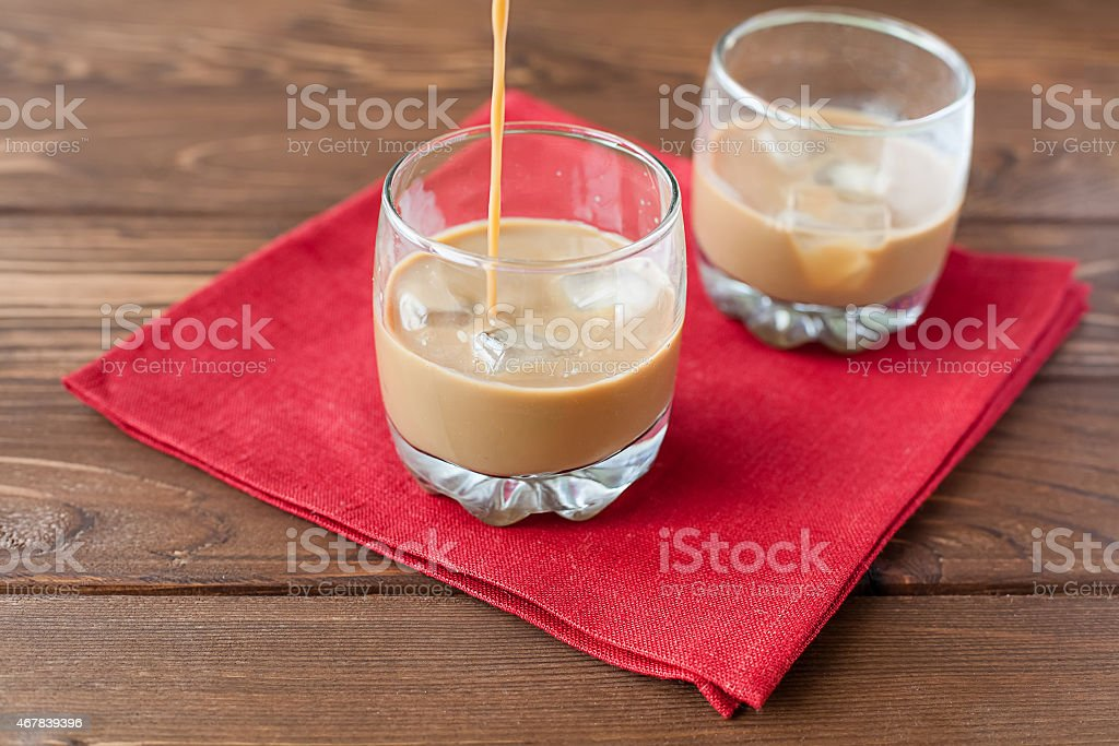 Coffee liqueur pouring in glass stock photo