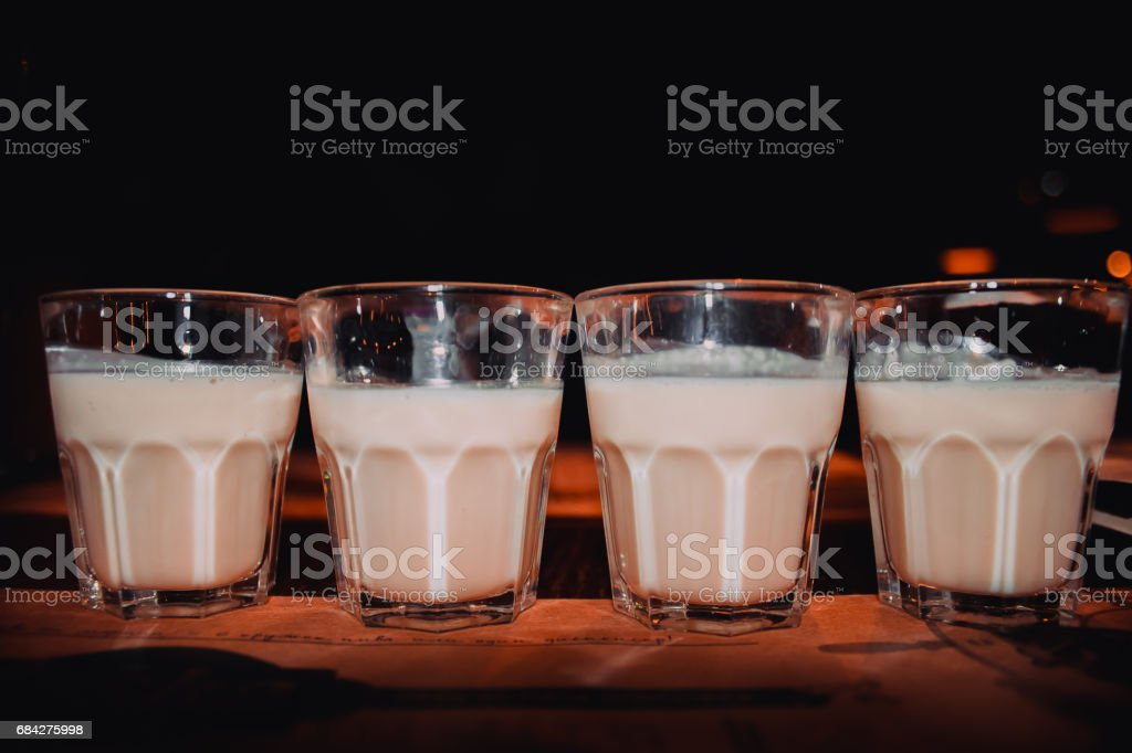 Coffee liqueur, shot glasses with homemade baileys, roasted coffee beans and chocolate, selective focus, toned image stock photo