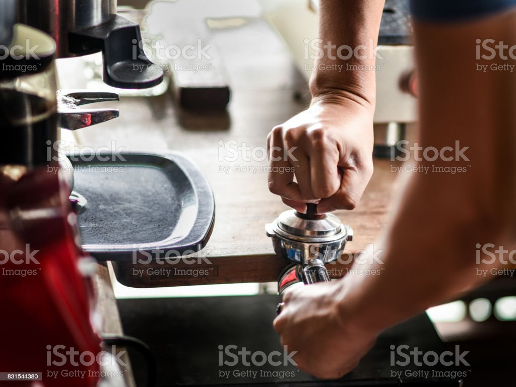 Coffee maker push the coffee powder in the espresso scoop stock photo