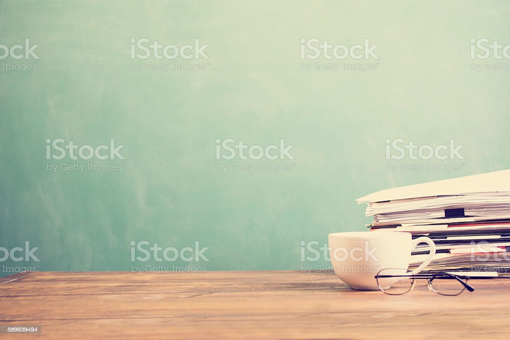 Coffee mug, papers stacked on teachers school desk with chalkboard. stock photo