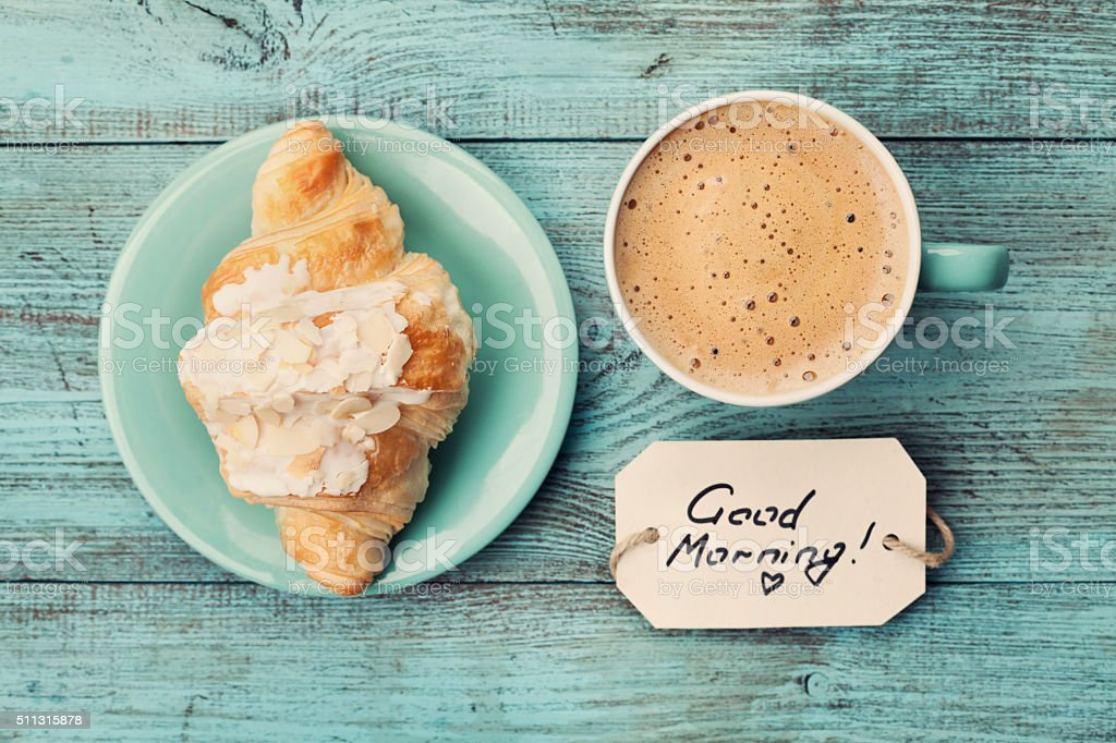 Coffee mug with croissant and notes good morning stock photo