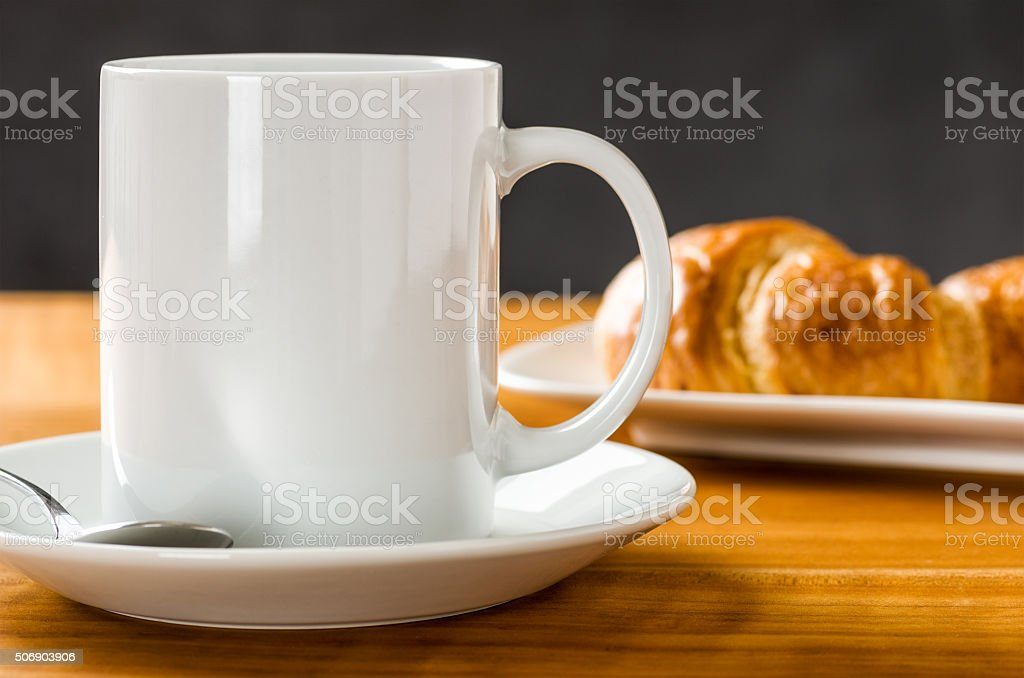 Coffee mug with croissants on a dark background stock photo