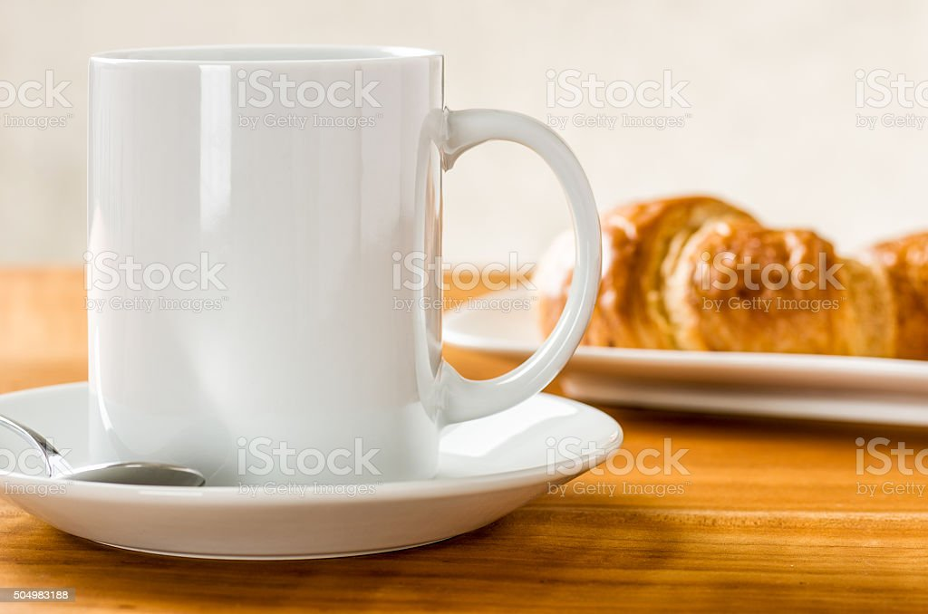 Coffee mug with croissants stock photo