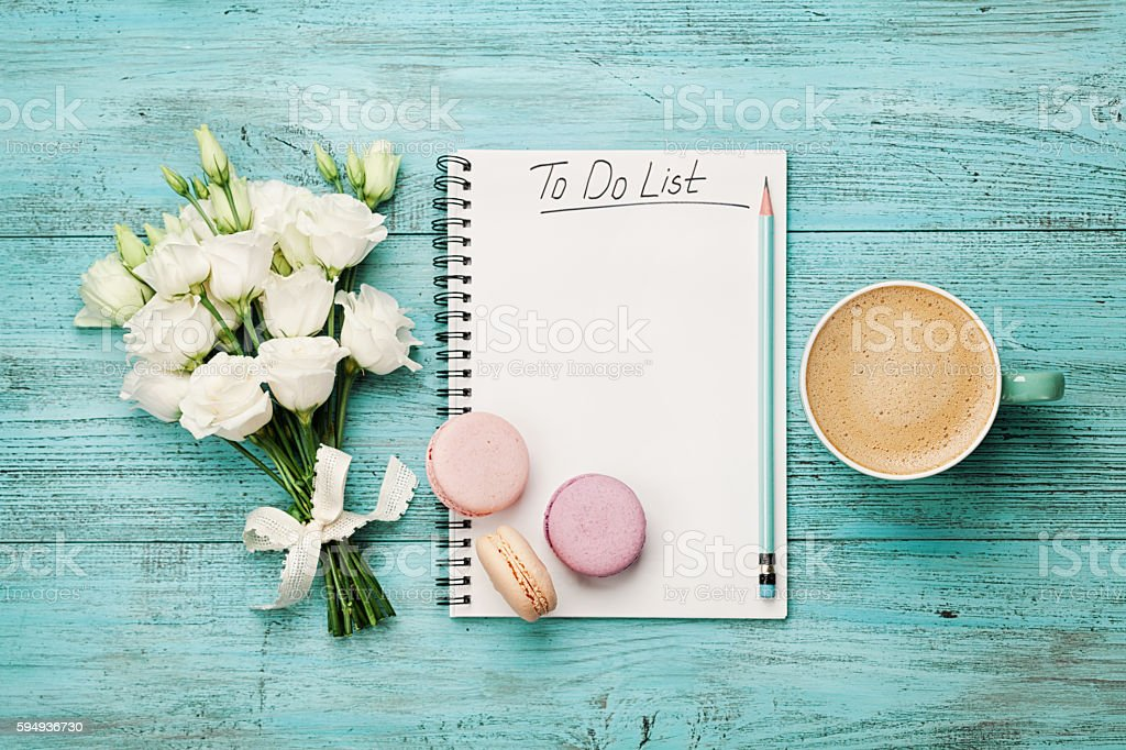 Coffee mug with macaron, white flowers and notebook. Flat lay. stock photo