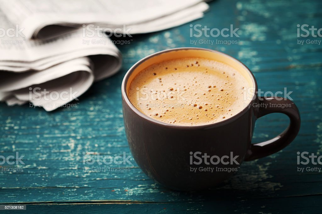 Coffee mug with newspaper on teal rustic table, cozy breakfast stock photo
