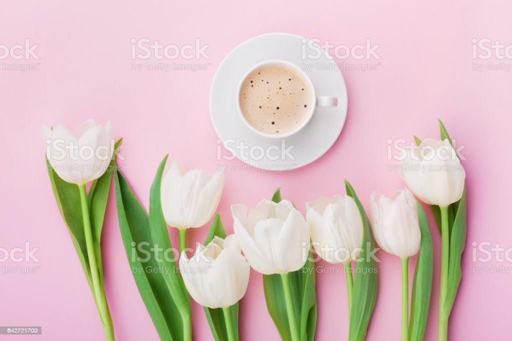 Coffee mug with spring tulip flowers on pink. Flat lay. stock photo