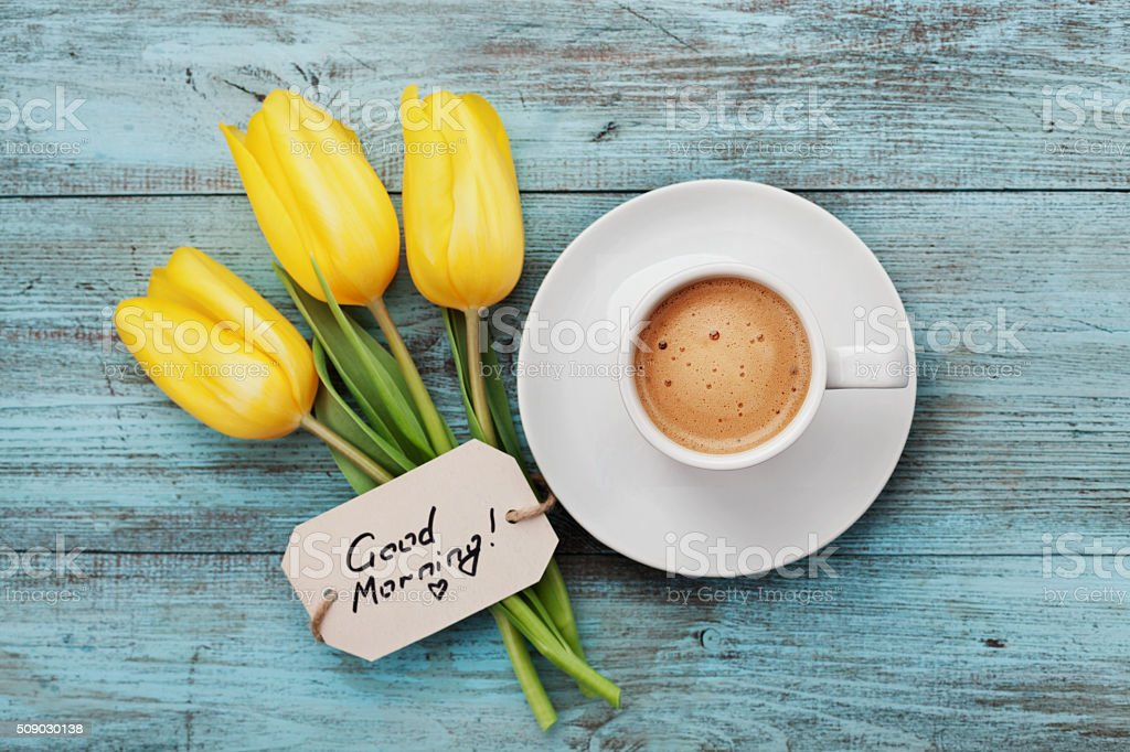 Coffee mug with yellow tulip flowers and notes good morning stock photo