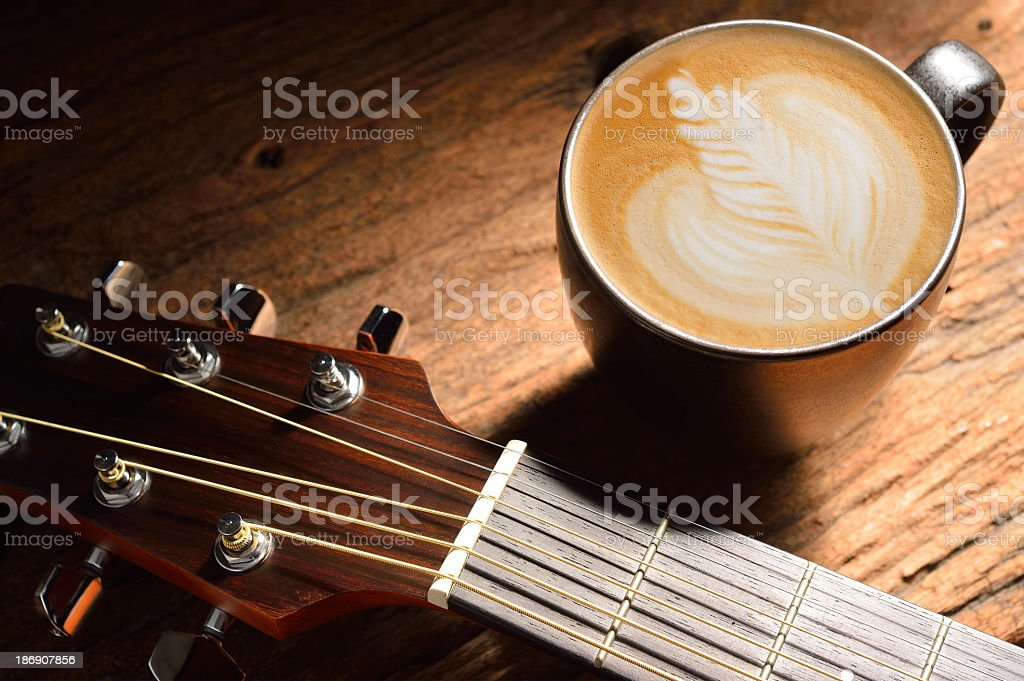 Coffee on wooden table with a guitar stock photo