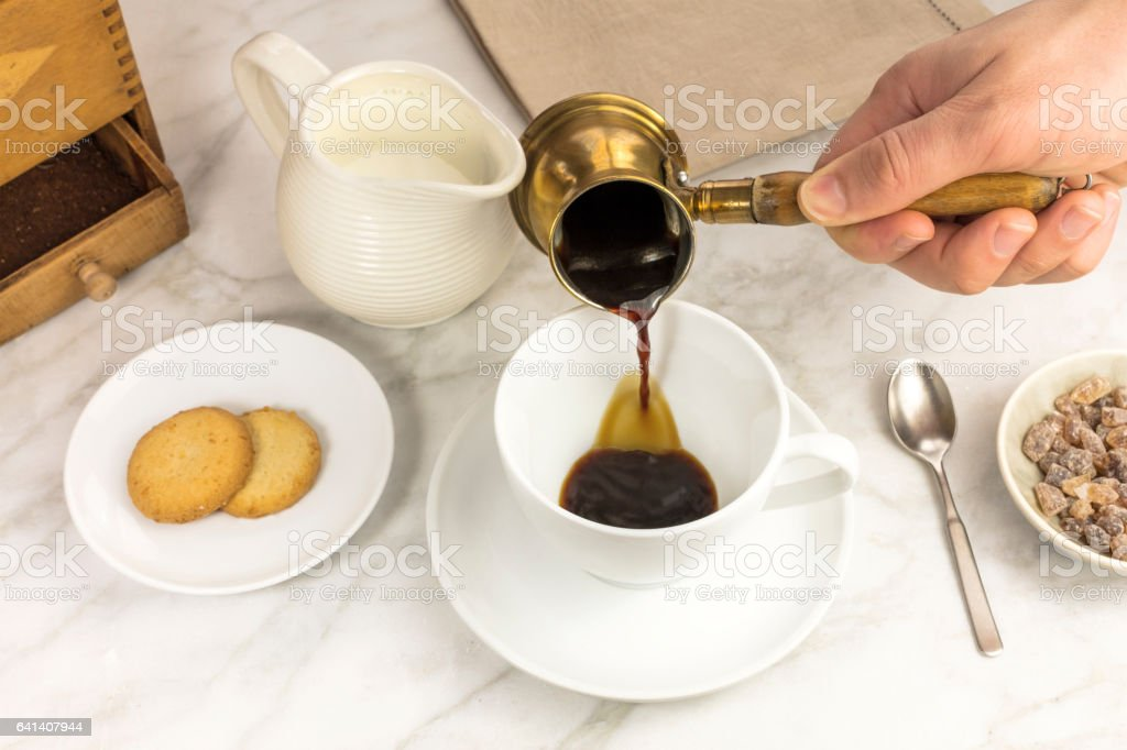 Coffee poured into cup, with milk jar and cane sugar stock photo