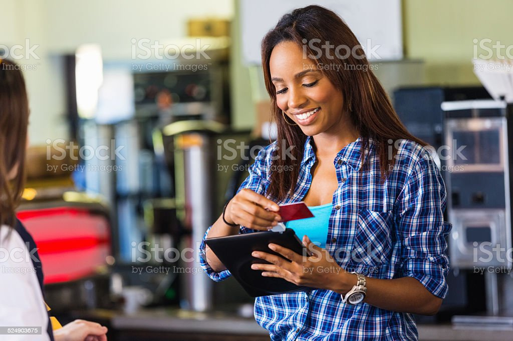 Coffee shop cashier swiping card on digital tablet reader stock photo
