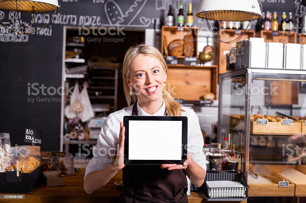 Coffee shop owner standing with blank screen tablet stock photo