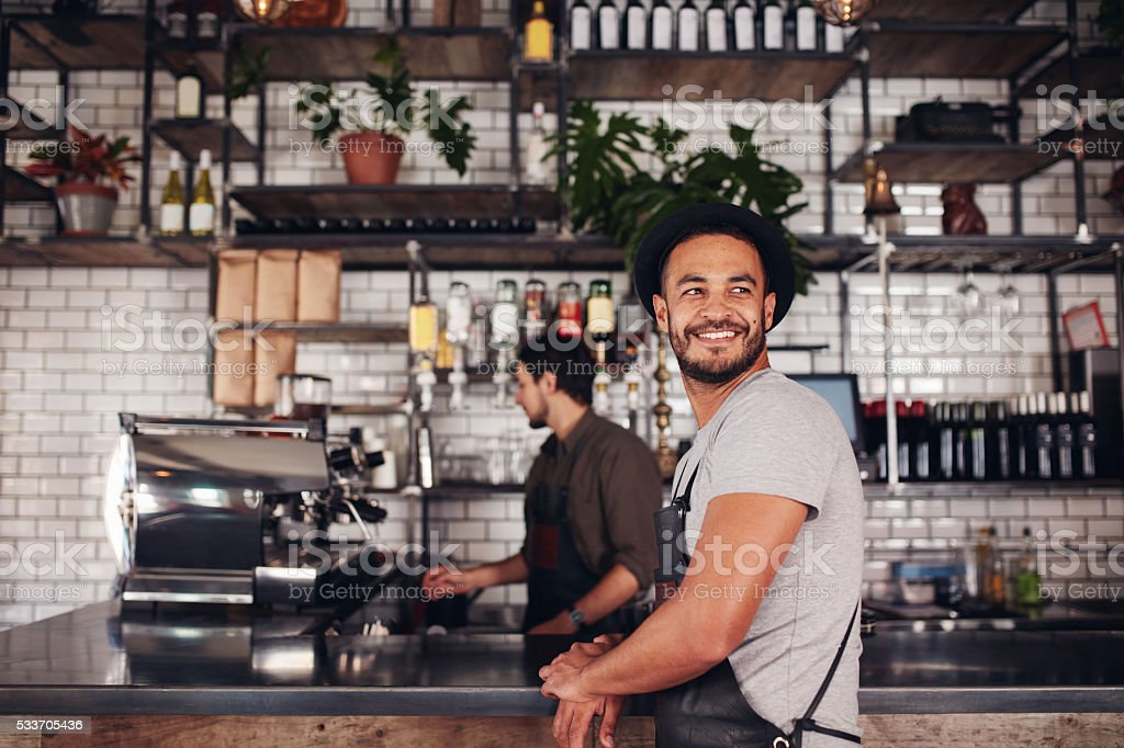 Coffee shop owner with barista working in behind stock photo