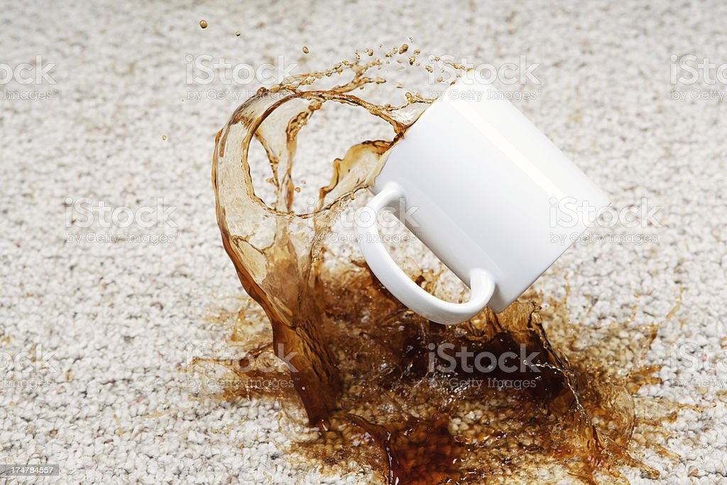 Coffee Spilling from Cup onto Carpet stock photo