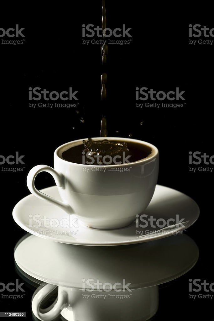 coffee splashing into white cup over black background royalty-free stock photo