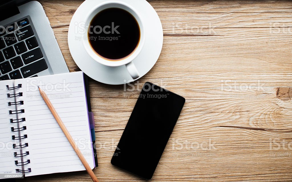 Coffee table with laptop, smart phone and notebook stock photo