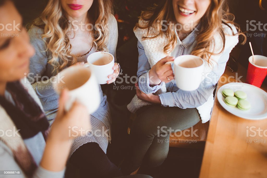 Photo of smiling friends sitting in a cafe and enjoying their time...
