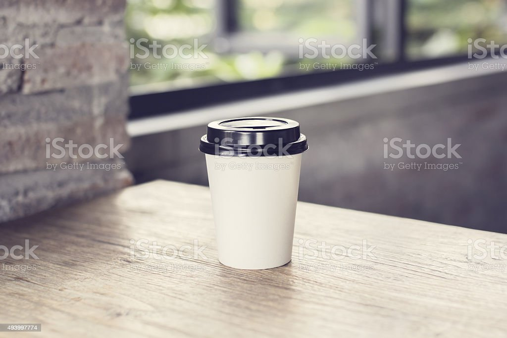 Coffee to go on a wooden table stock photo