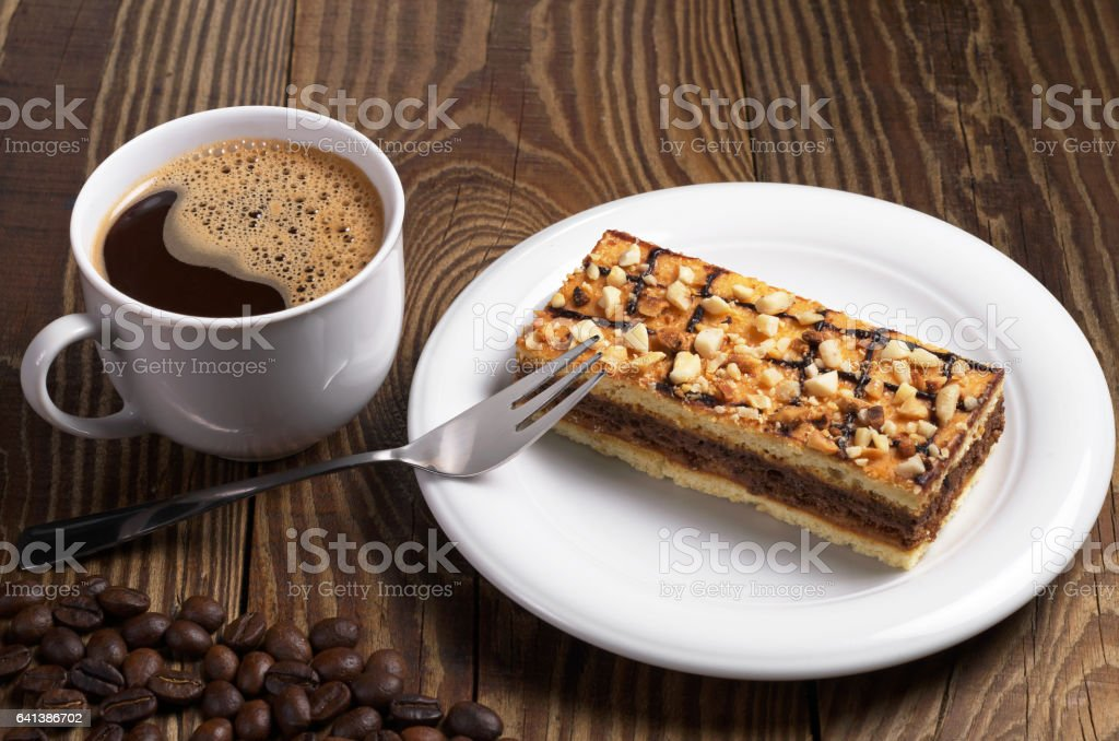 Cup of hot coffee and sweet caramel cake with nuts on wooden table