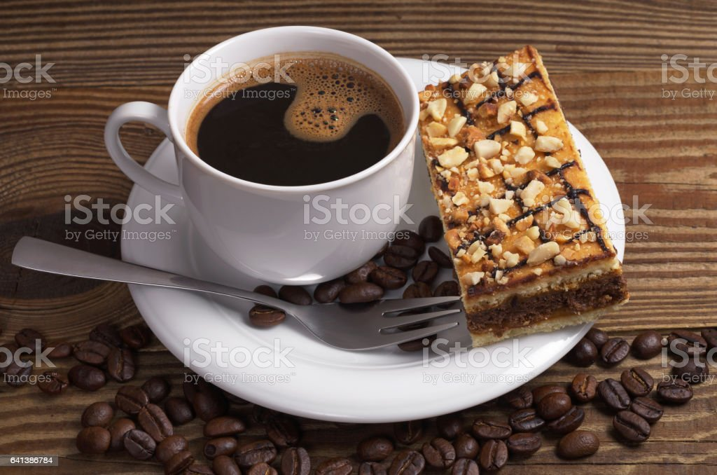 Cup of hot coffee and caramel cake with nuts on wooden table