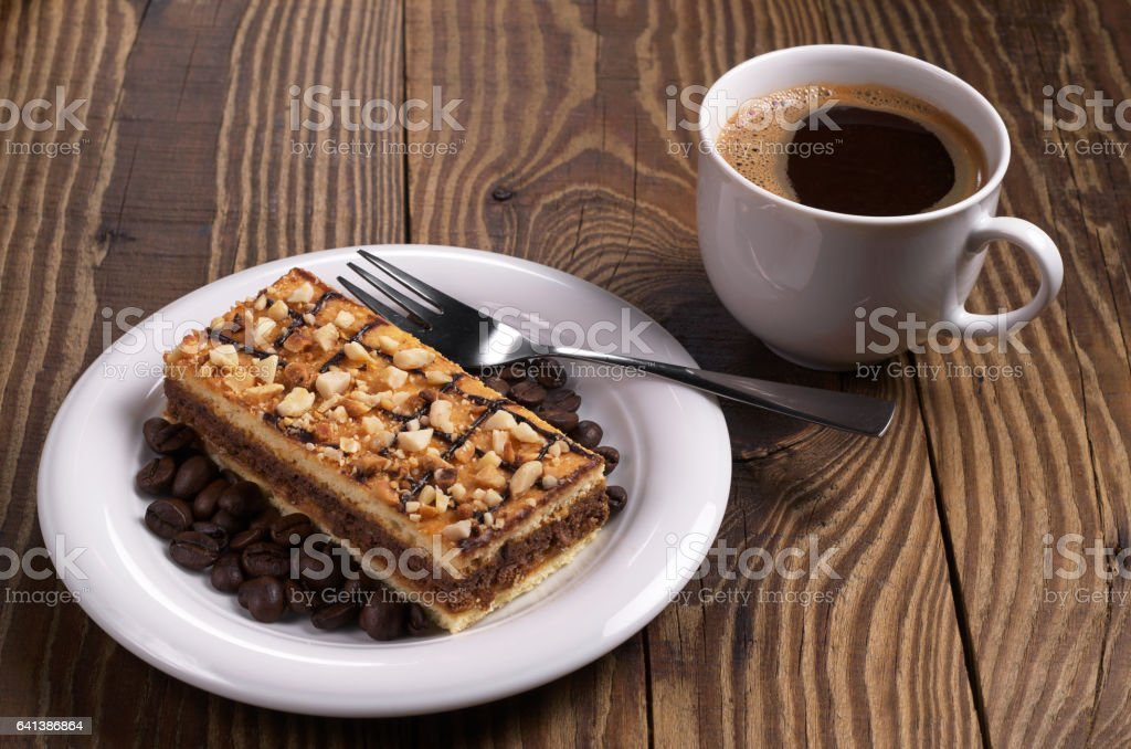 Cup of hot coffee and delicious caramel cake with nuts on wooden table