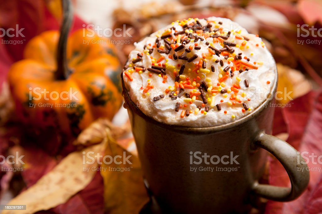 Coffee with cream and sprinkles next to a pumpkin stock photo