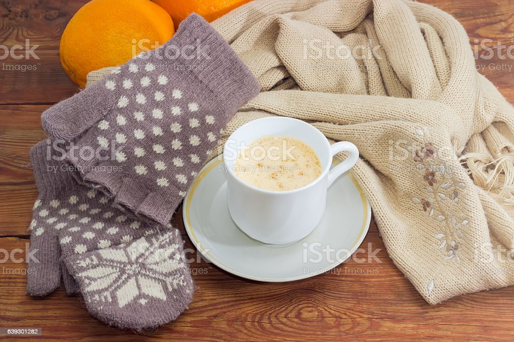 Coffee with cream on background of woolen mittens and scarf stock photo