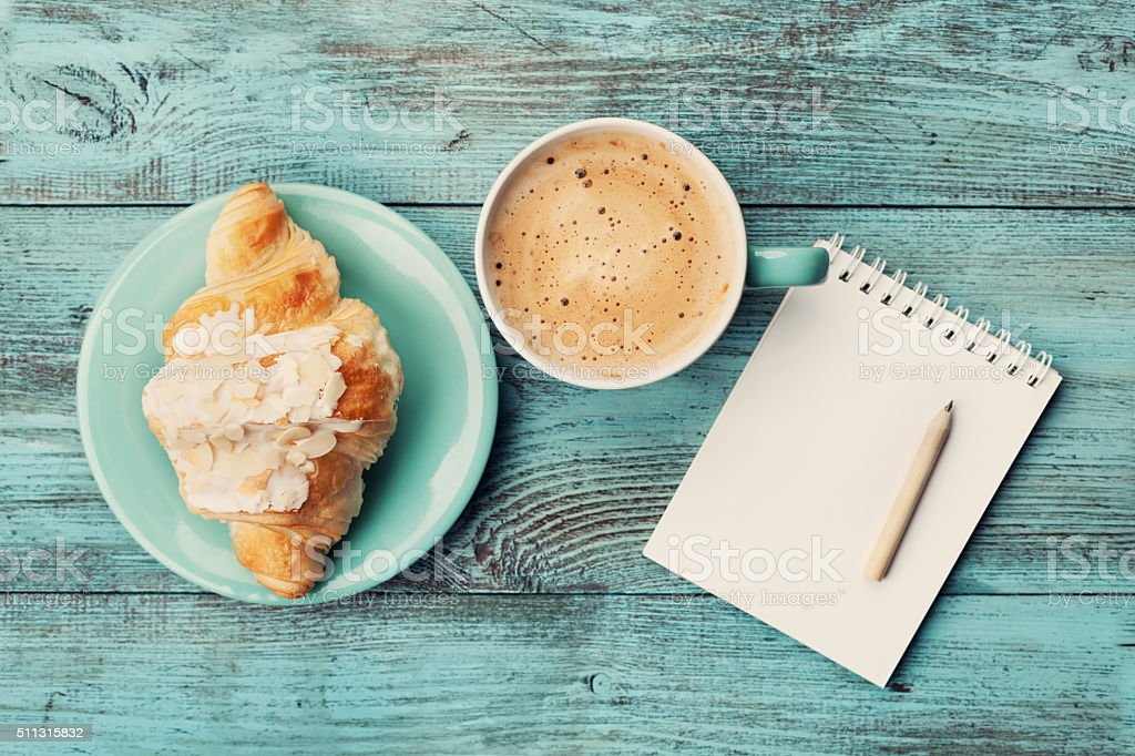 Coffee with croissant and notebook for business plan and design stock photo