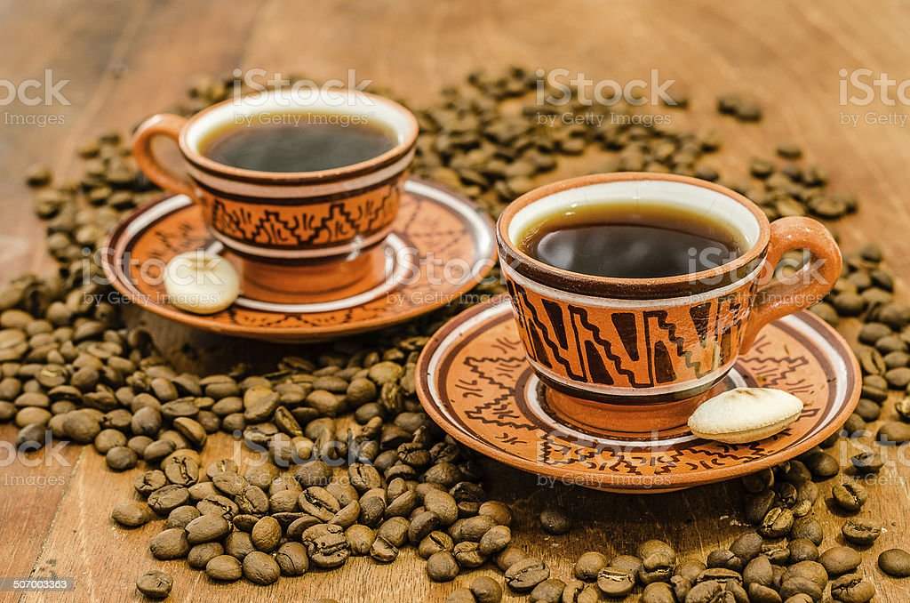 Coffee with steam, grains on a wooden table royalty-free stock photo