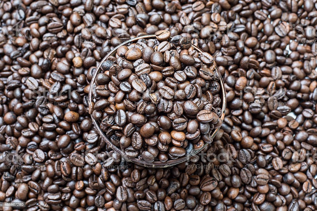 Coffeebean in cup, on coffeebeans background stock photo