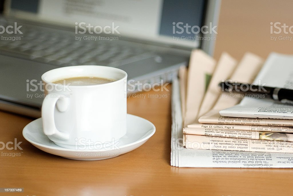 Coffee,laptop,newspaper and a fountain pen on table stock photo