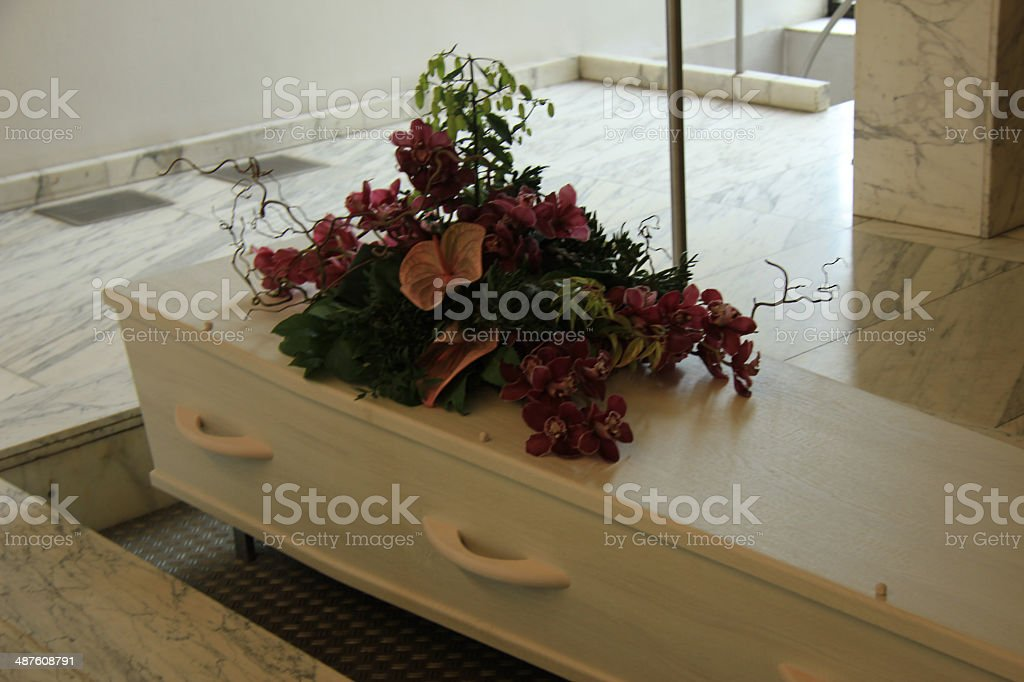 Coffin with funeral flowers stock photo