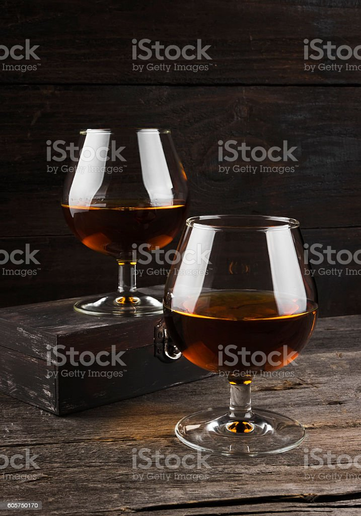 Cognac in two glasses on a dark wooden background stock photo