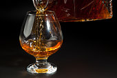 Cognac is poured from a bottle into  glass