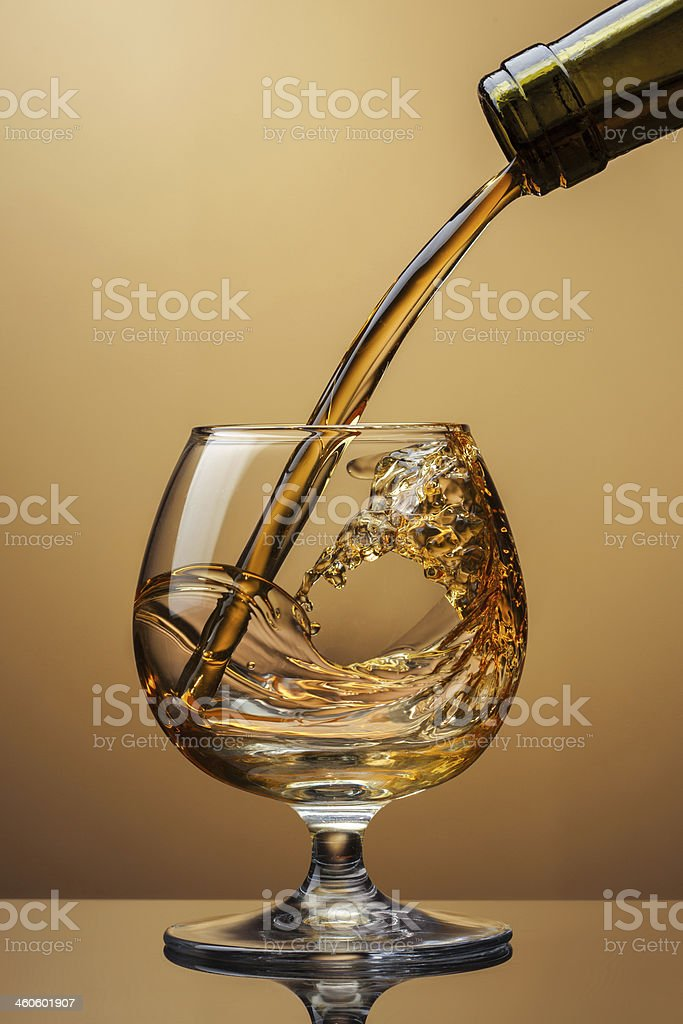 Cognac pouring from bottle into glass with splash on brown stock photo