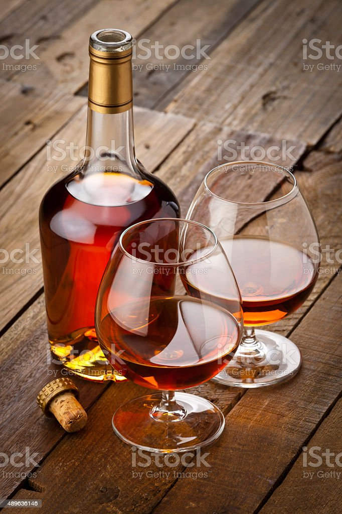 Cognac snifter with bottle on rustic wood table stock photo