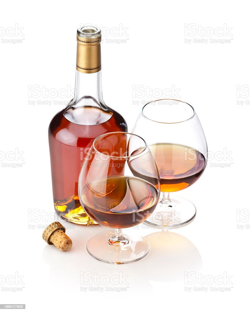 Cognac snifters with bottle on reflective white background stock photo