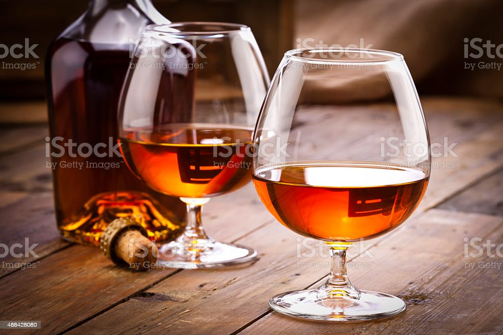 Cognac snifters with bottle on rustic wood table stock photo