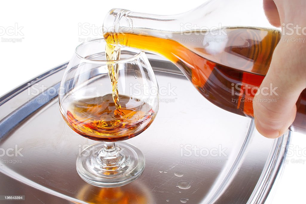 Cognag pour into the glass royalty-free stock photo