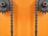 Cogwheels and double chain on orange background with empty space