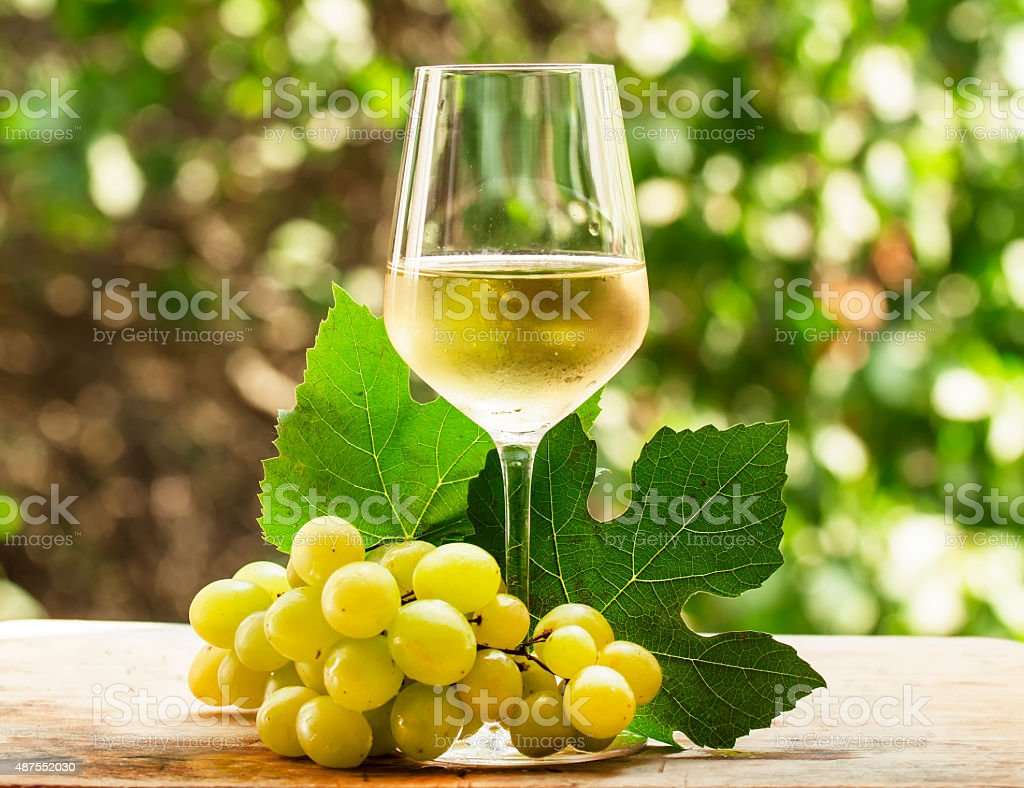 Coid white wine and green grapes on natural blurred background stock photo