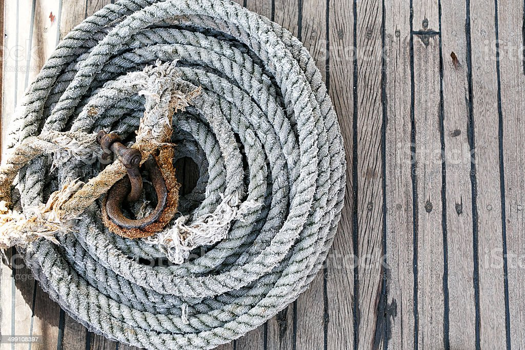 Coiled rope on a wooden deck stock photo