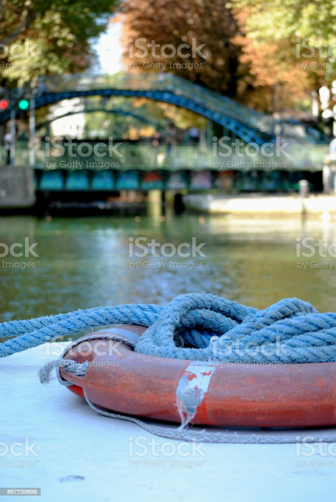 Coiled rope on bow of boat in canal stock photo
