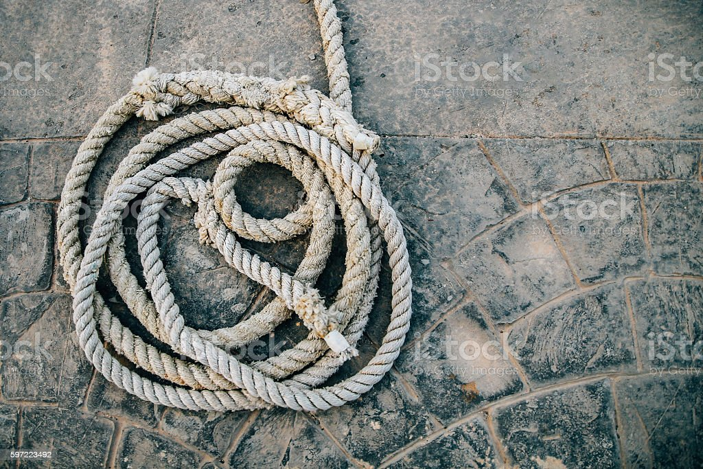 Coiled rope on concrete background stock photo