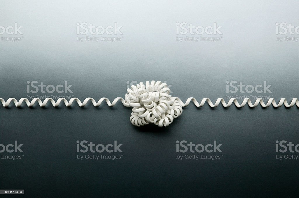 Coiled telephone cord tied in a knot on gray background stock photo