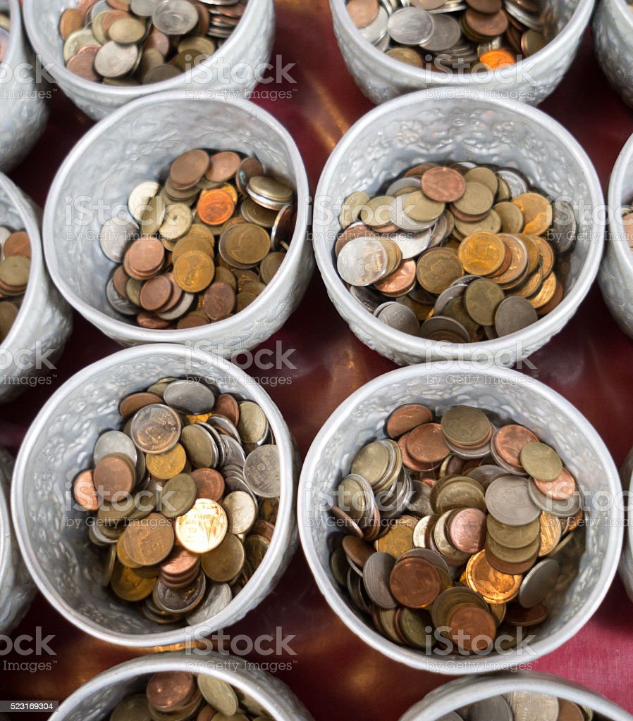 Coin in the donation bowl stock photo