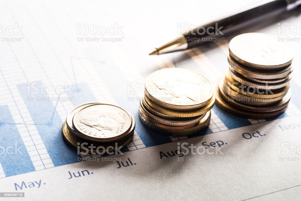 Coin money stacked growing with pen on document graph.financial stock photo