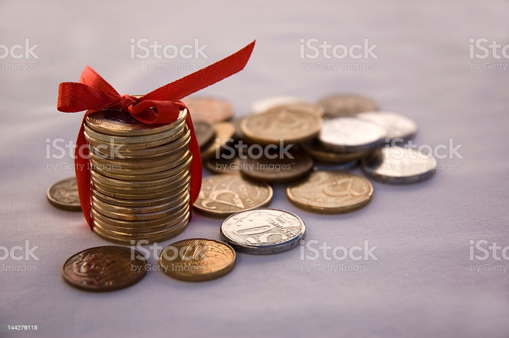 Coin pile tied together with red bow with other coins around stock photo